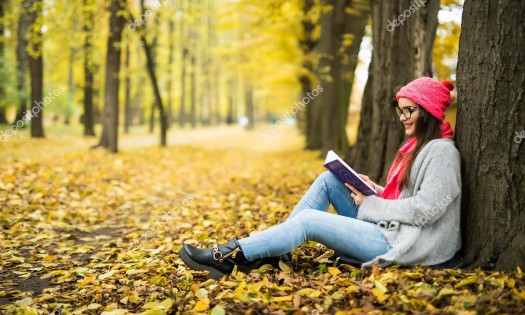 Beautiful young brunette sitting on a fallen autumn leaves in a park, reading a book